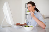 Casual brunette businesswoman eating a salad at her desk