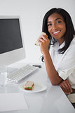 Pretty businesswoman having a sandwich at her desk
