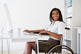 Smiling businesswoman in wheelchair working at her desk