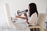 Angry businesswoman shouting in megaphone at phone