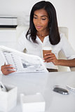 Pretty businesswoman reading newspaper at her desk