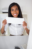 Pretty businesswoman showing white card at her desk