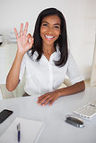 Pretty businesswoman making ok sign to camera at her desk