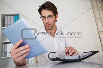 Casual businessman organizing his schedule at his desk