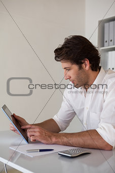Casual focused businessman using tablet and calculator