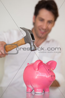 Casual businessman breaking piggy bank with hammer