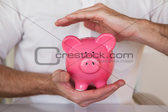 Casual businessman holding piggy bank