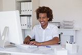 Casual smiling businessman in wheelchair working at his desk