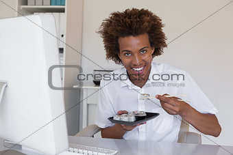 Casual smiling businessman eating sushi at his desk