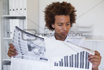 Casual focused businessman reading newspaper at desk