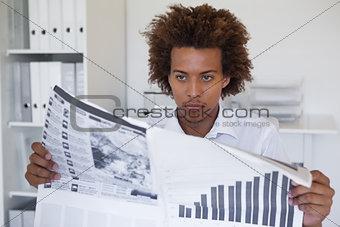 Casual focused businessman reading newspaper at desk