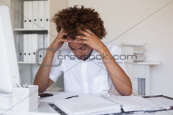 Casual stressed businessman with his head down at desk
