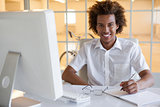 Casual young businessman writing at his desk smiling at camera