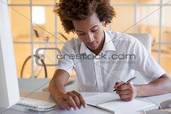 Casual young businessman writing at his desk smiling