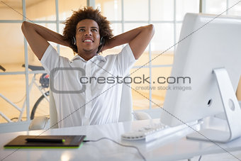 Smiling young businessman using digitizer and headset at desk