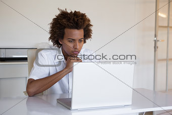 Focused casual businessman using laptop at desk