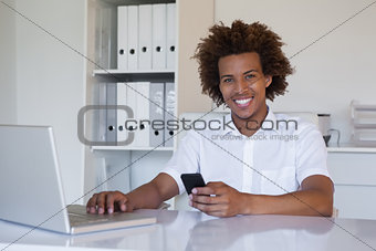 Casual smiling businessman using his smartphone and laptop at his desk