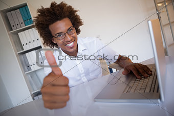Casual businessman smiling at camera at his desk showing thumbs up