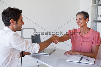 Casual business people shaking hands at desk
