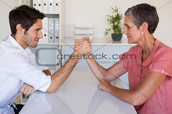 Casual business team arm wrestling at desk