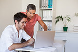 Casual business team working together at desk using laptop