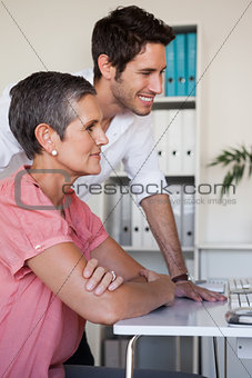 Casual business team working together at desk using computer