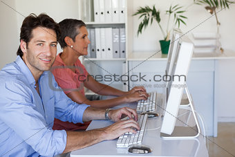 Casual business team working at desk using computers