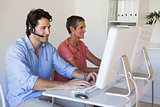 Casual business team working at desk using computers with man using headset