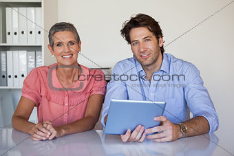 Casual smiling business team working at desk using tablet