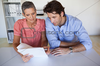 Casual smiling business team working at desk reading document