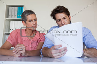 Casual business team working at desk reading document