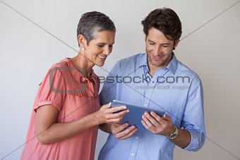 Casual smiling business team looking at tablet pc together