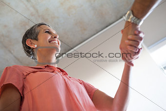 Casual smiling businesswoman shaking hands