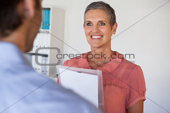 Casual smiling businesswoman looking at colleague