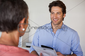 Casual smiling businessman looking at colleague