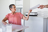 Casual businesswoman handing document to colleague
