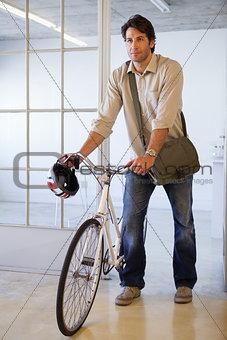 Casual businessman pushing his bike