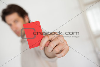 Casual businessman showing red card