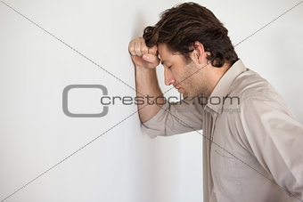 Casual worried businessman leaning head on wall