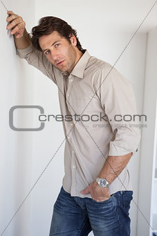 Casual worried businessman leaning on wall