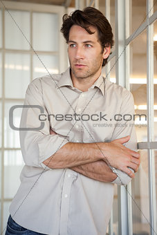 Casual worried businessman leaning on window