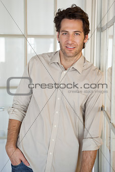 Casual smiling businessman leaning on window