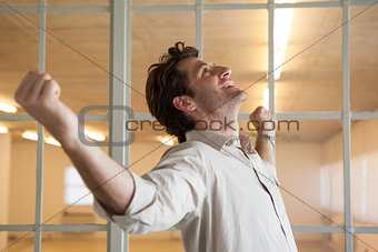Casual smiling businessman with arms outstretched
