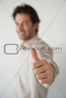 Casual smiling businessman showing thumbs up to camera