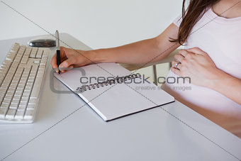 Casual pregnant businesswoman writing at her desk