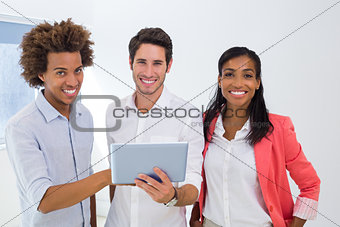 Three colleagues working on tablet pc smile to camera