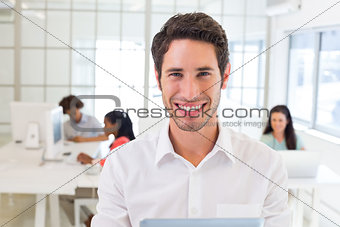 Businessman with tablet pc smiles to camera