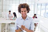 Casual businessman taking notes smiling at camera