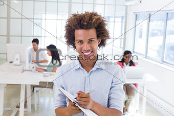 Casual businessman taking notes smiling at camera