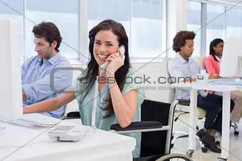 Attractive businesswoman in wheelchair on phone